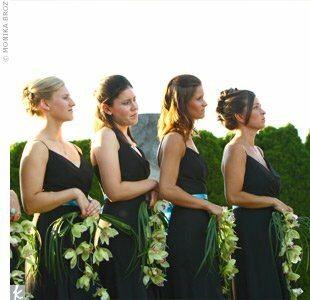 Lauren's six bridesmaids wore long, flowing, black chiffon dresses with an aqua blue ribbon around the waist. Each held a small bundle of long-stemmed green grass and lime green orchids.