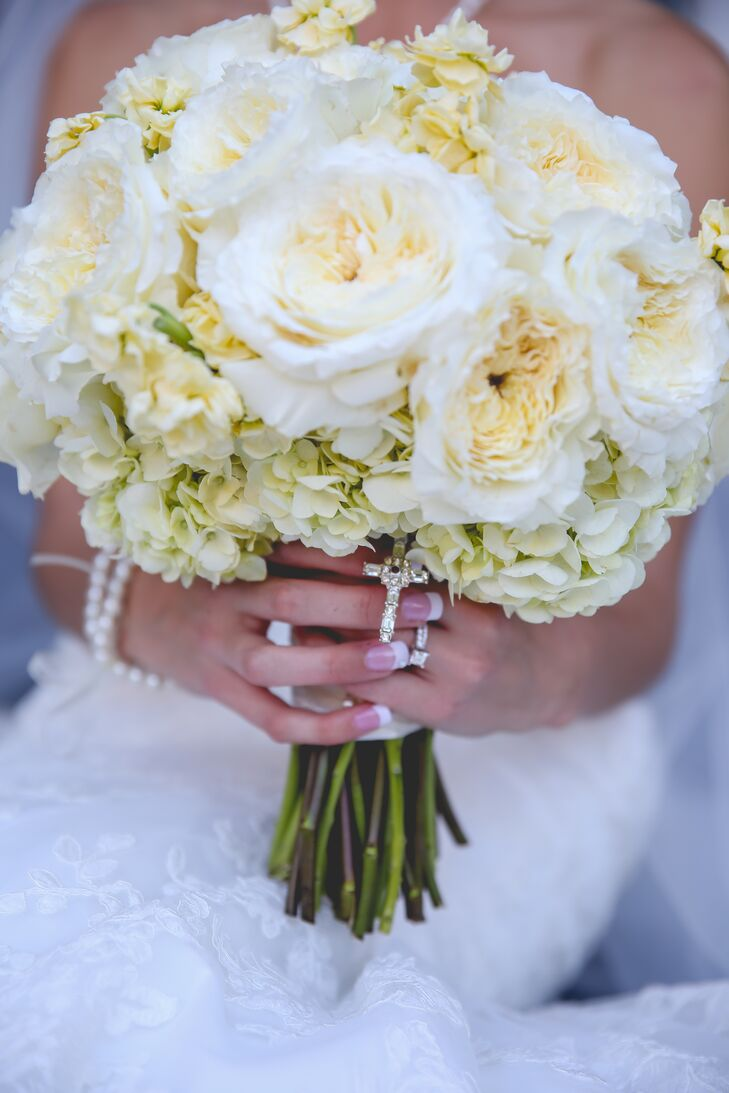 Lauren carried ivory garden roses and hydrangeas in her classic bouquet. She added a cross around the stems for her religious ceremony.