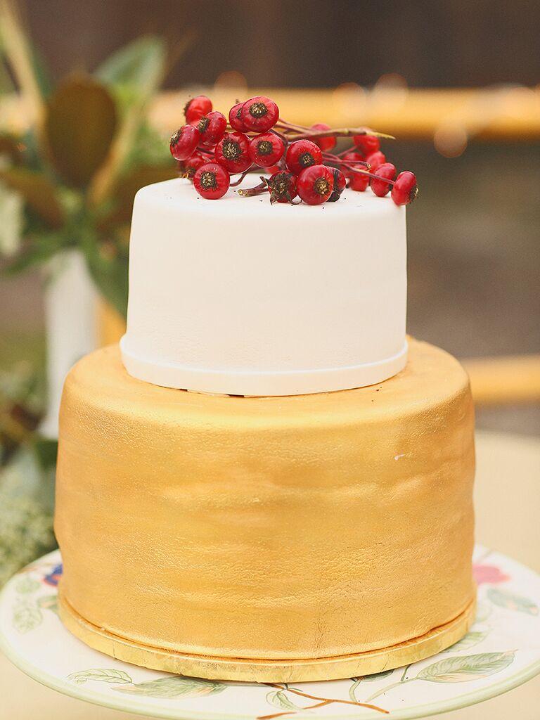 Gold and white fondant wedding cake with berry garnish