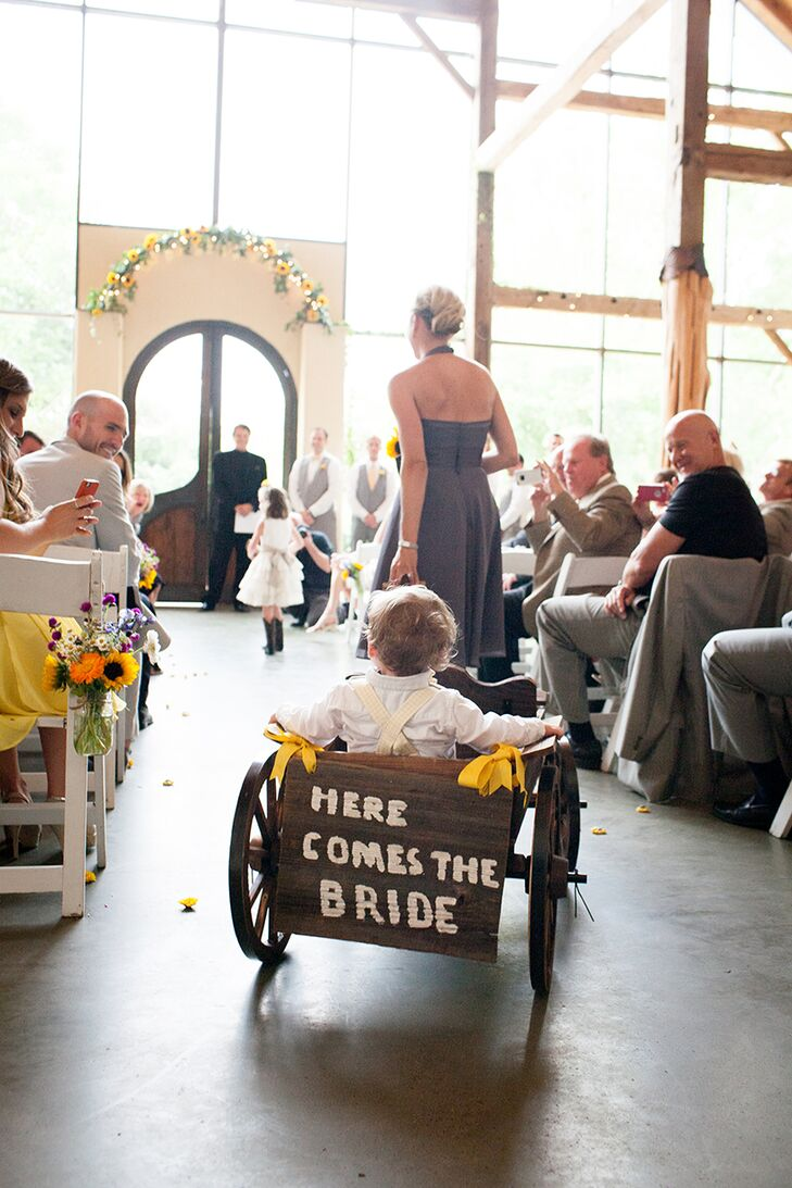 """One of Carly's favorite elements was the antique wooden wagon, which carried her toddler nephew and ring bearer down the aisle. On the back was painted """"Here Comes The Bride!"""""""