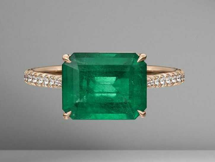 East-west emerald engagement ring with pavé band