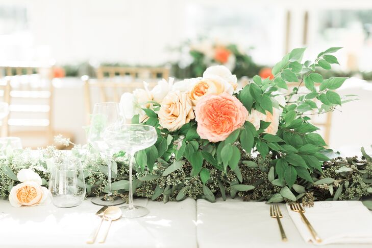 Lush, textured arrangements of eucalyptus and garden roses gave the tablescape an organic beauty.