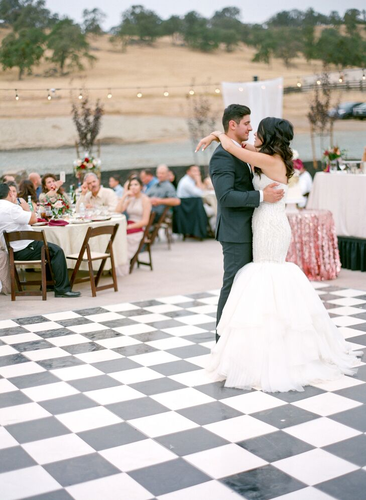 "A stunning black and white dance floor added a glamorous edge to the romantic outdoor reception. ""The reception was filled with lots of dancing to cultural music,"" Marina says."