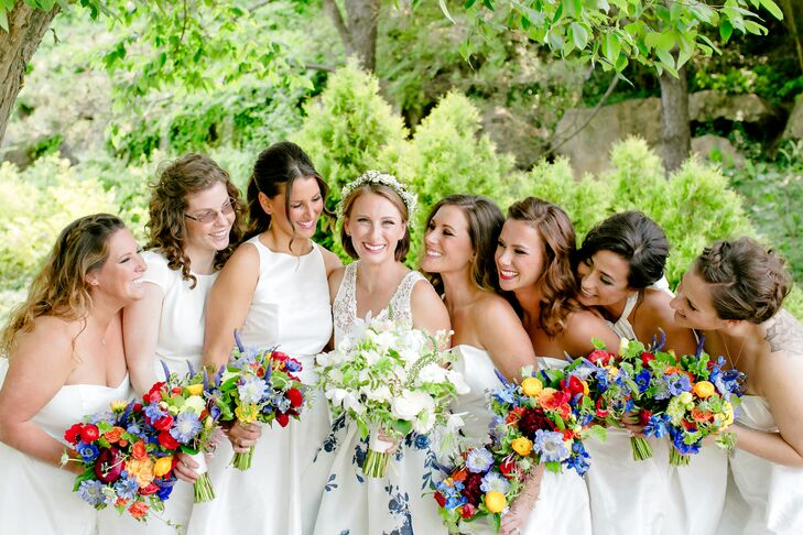 Since white was the matching color to the bold blue, Maggie's bridesmaids wore white dresses with gold shoes and sapphire earrings. Each carried a vivid display of spring blooms in their bouquets, while Maggie kept it classic with all-white flowers and soft greenery.