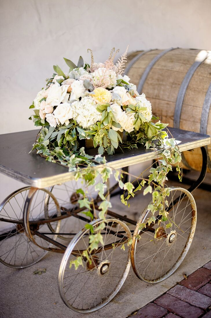 A wooden table on wheels added a touch of rustic ambience to the outdoor reception decor. On top of the wood was an overflowing flower arrangement, filled with a variety of neutral-color roses, hydrangeas and peonies.