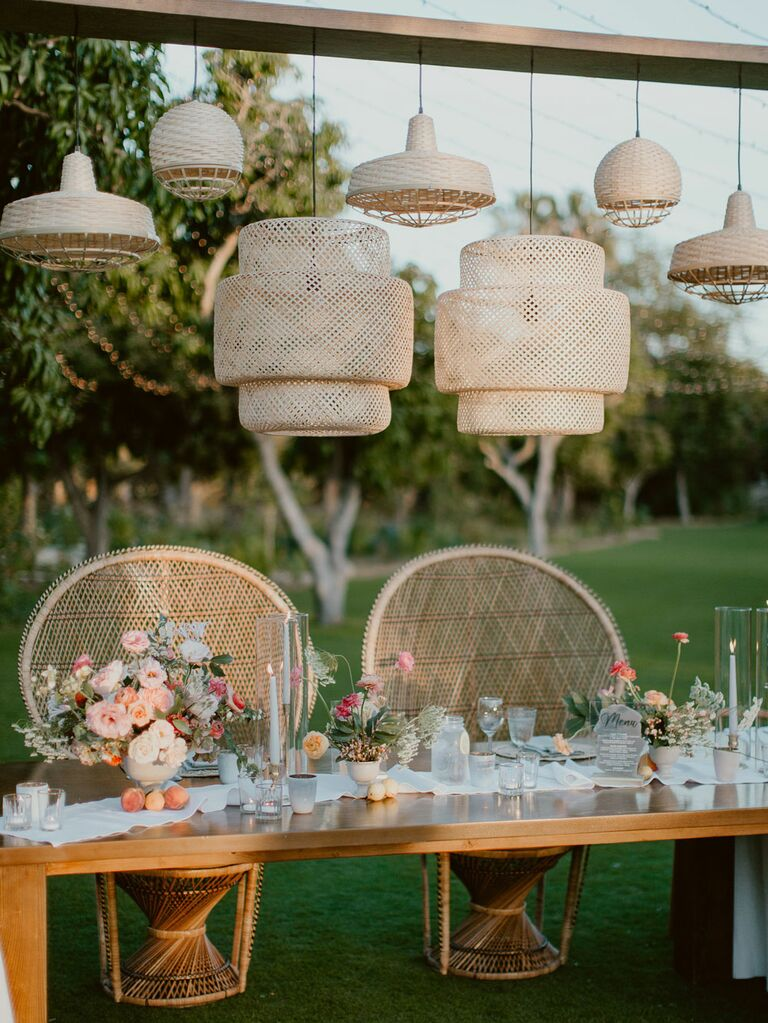 Boho sweetheart table with retro peacock chairs and rattan hanging lights