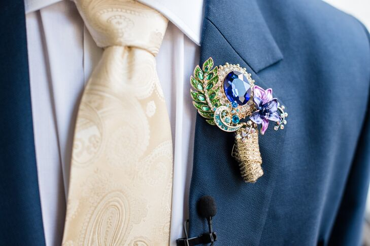 Chintan's peacock-inspired brooch boutonniere complemented his navy suit, a custom design from Mumbai, India.