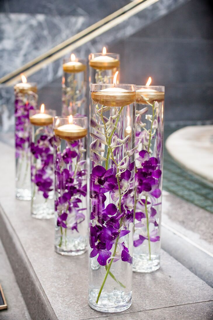 Glass vases were filled with purple orchids and floating gold candles for a romantic touch.