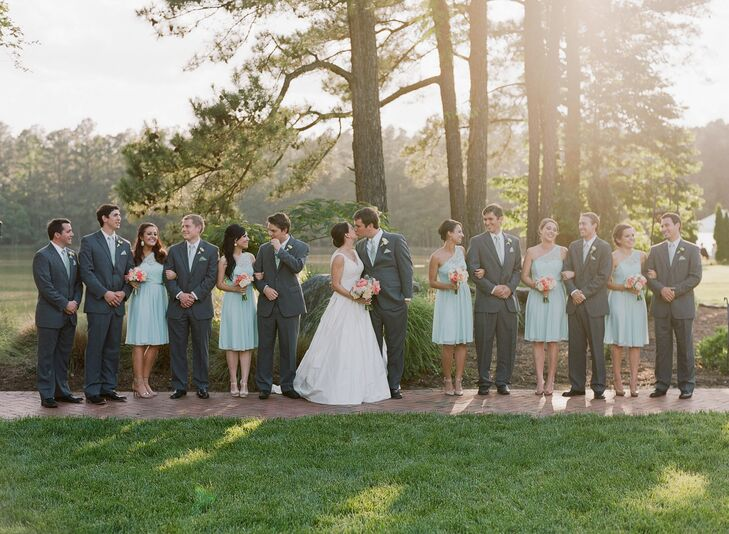 """Katharine chose a sophisticated springtime look for her bridesmaids. They wore matching knee-length dresses with one-shoulder necklines embellished with ladylike mint green, which they paired with their own metallic shoes. """"I was originally going for a different dress but noticed the lace top on this one and thought it would fit well with mine,"""" she says."""