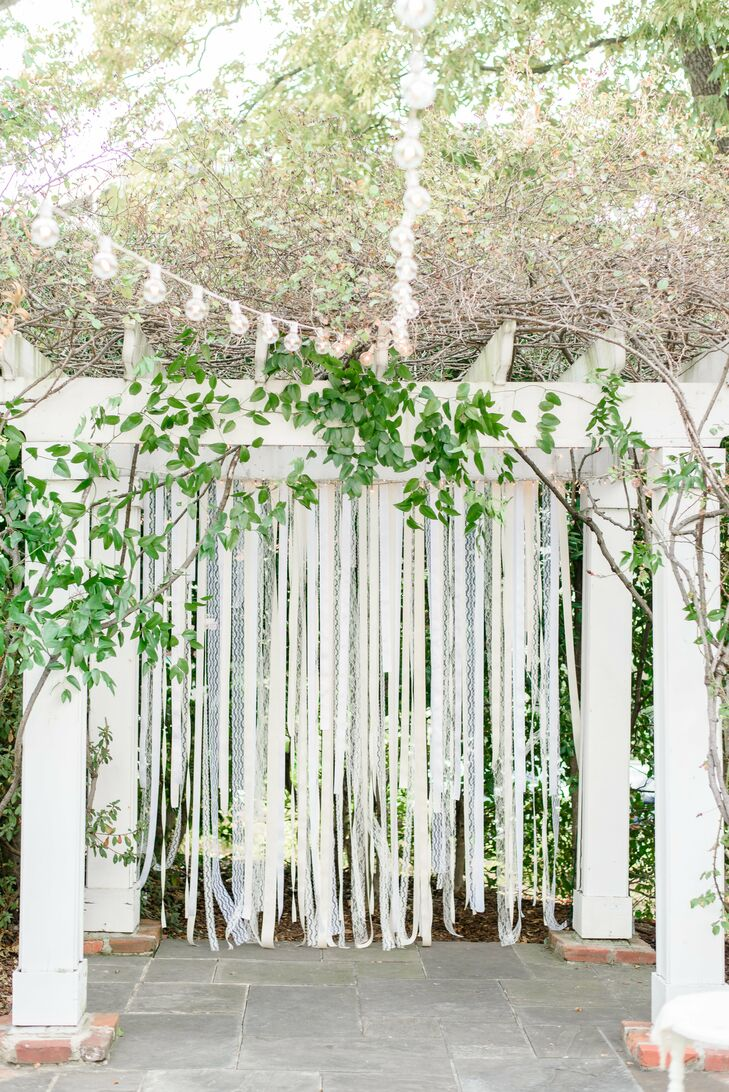 The couple exchanged vows on Manor House's lawn under a pergola that they had draped with ribbons of ethereal lace.