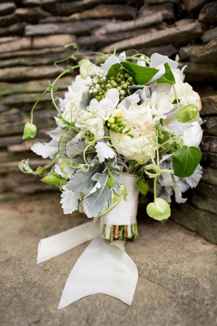 Garden roses, peonies, freesia, snowball viburnum and dusty miller filled Brigid's ribbon-wrapped bouquet.