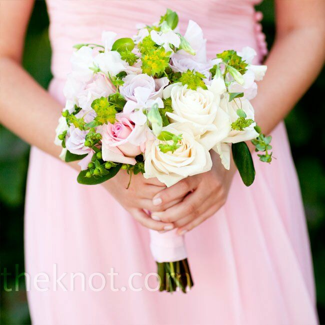 The bridesmaids carried pale-pink and ivory roses mixed with greenery and berries for texture.