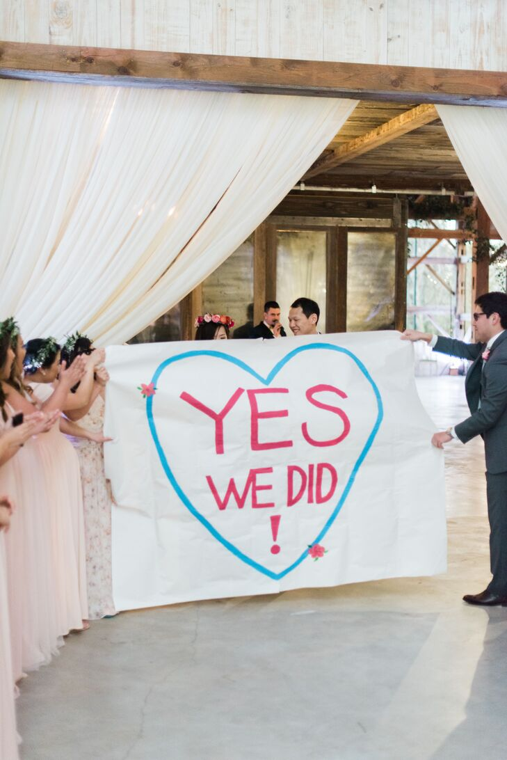 """For their grand entrance, Deborah and Elton burst into their barn reception like champions, ripping through a paper banner that read """"Yes, we did!"""""""