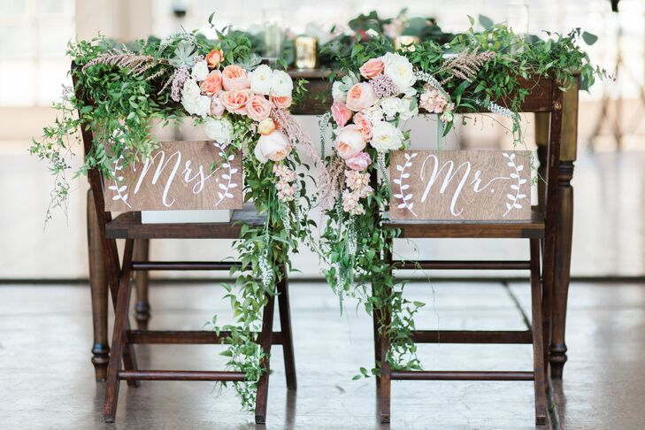 At the reception at Wind Mountain Ranch in Stevenson, Washington, green fern garlands with blush and peach peonies adorned Eliza and Jake's chairs at the head table.
