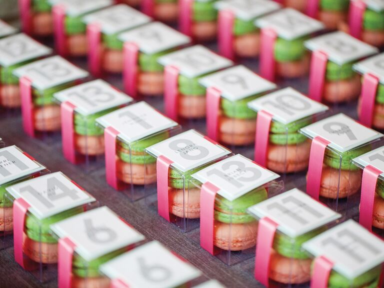 Pink and green macarons in boxes escort cards