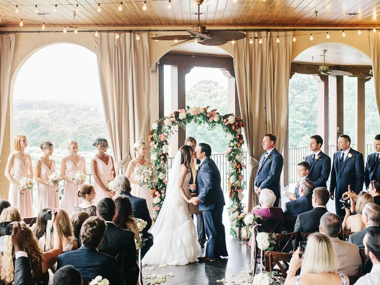 Indoor summer wedding ceremony with string lights and garland wedding arch