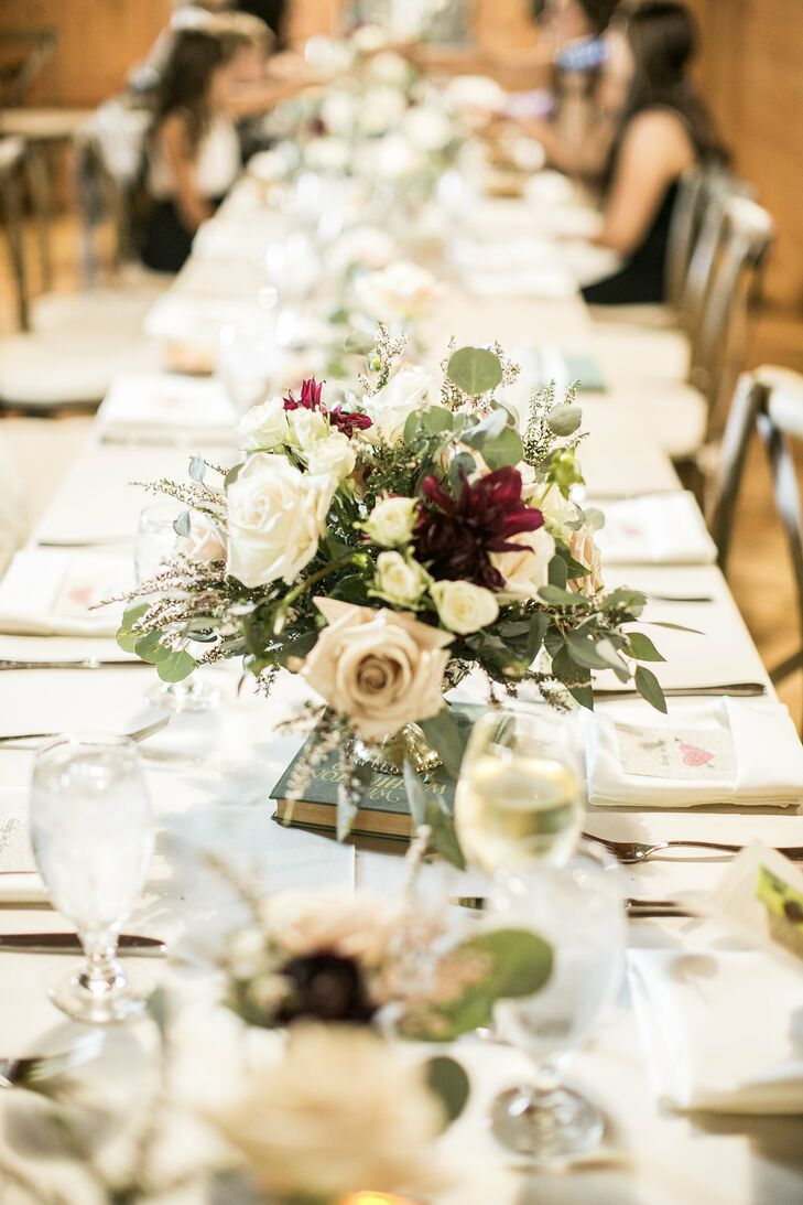 Farm tables were dressed with white linens and floral arrangements of ivory, purple and blush.