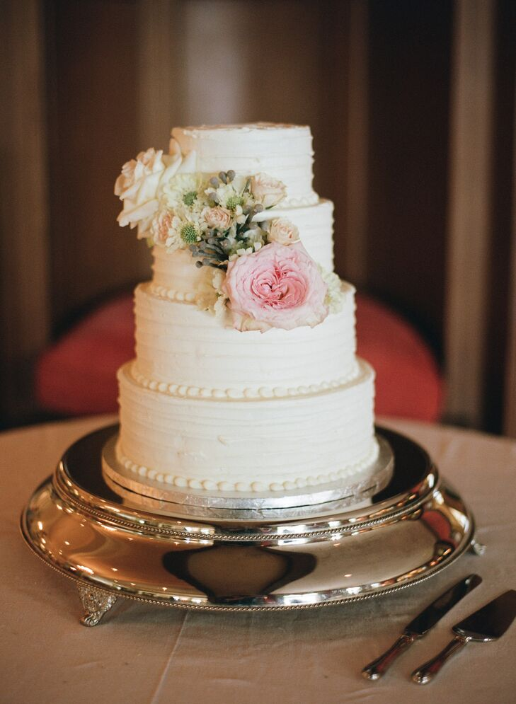The couple enjoyed a four-tier banana cake with rum buttercream frosting. It was decorated with blush and ivory flowers to match the romantic wedding look.