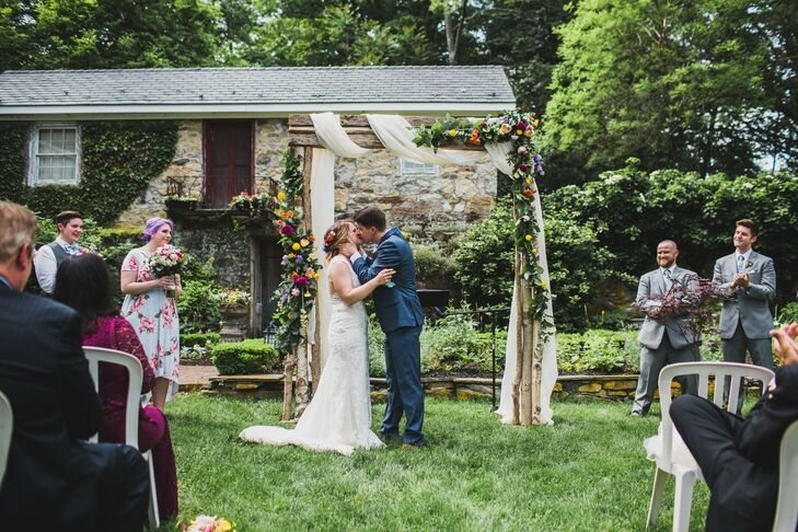 First Kiss in Front of Draped Wedding Arch at Crossed Keys Estate