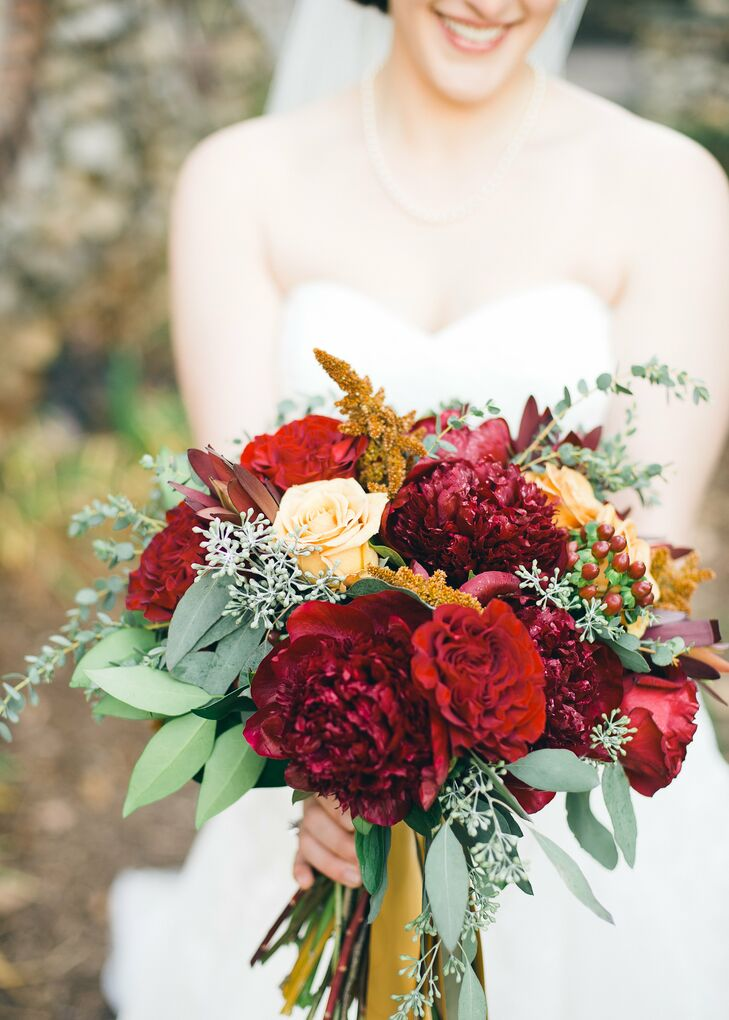 Ellie's bridal bouquet was filled with dark red and yellow roses, hypericum berries and eucalyptus.