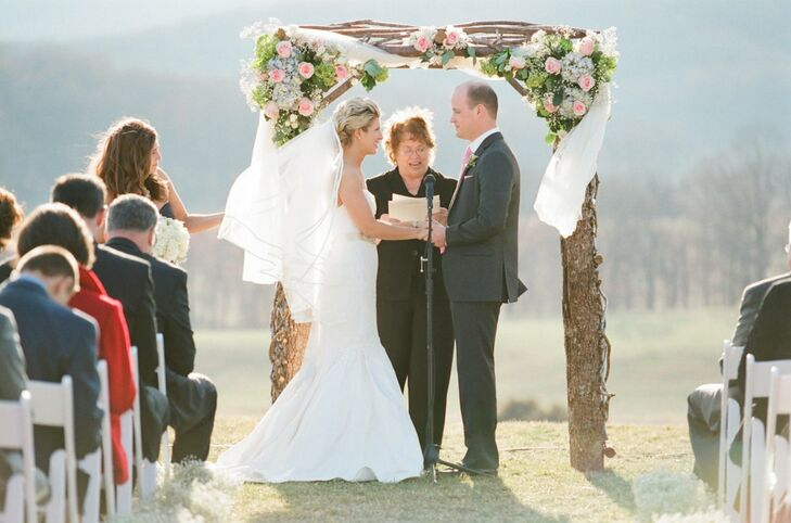 The couple exchanged their vows in from of a twisted branch wedding arch decorated with pastel roses and hydrangeas.