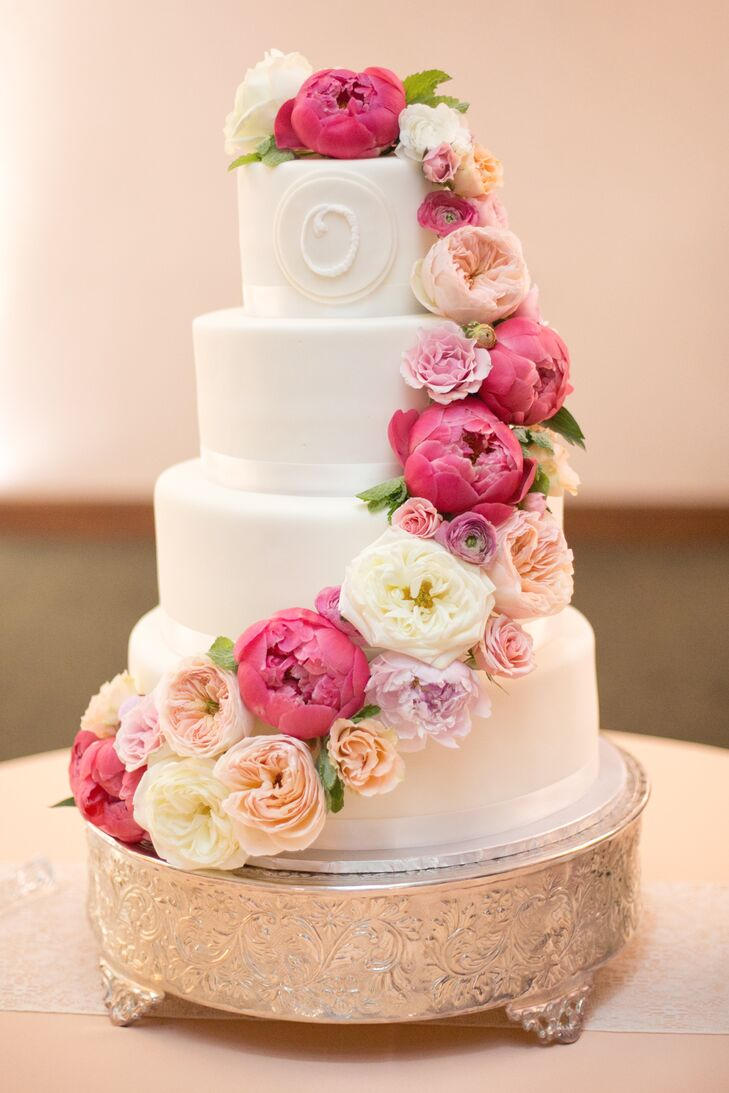 The stunning buttercream cake was decorated with cascading vibrant peonies and their married initial.