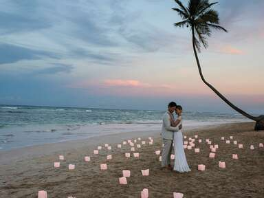 man in suit with woman in wedding dress on the beach among candles and a palm tree