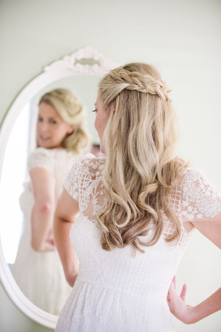 "Hair and makeup artist Pam Geiger used a curling iron to give Jill loose natural waves. She then took two sections of hair from the front and worked them into a braid, which wrapped around the crown of Jill's head, adding in a few small flowers as a decorative touch. ""I always knew I wanted to wear my hair the way I did on my wedding day, so it didn't hurt that the feel of the dress was a perfect match!"" says Jill."
