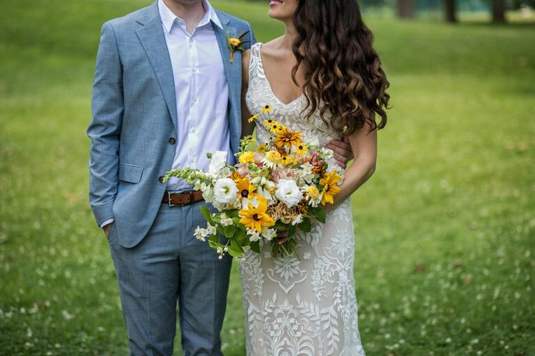 Bride holding wildflower-inspired bouquet with Black-eyed Susan blooms