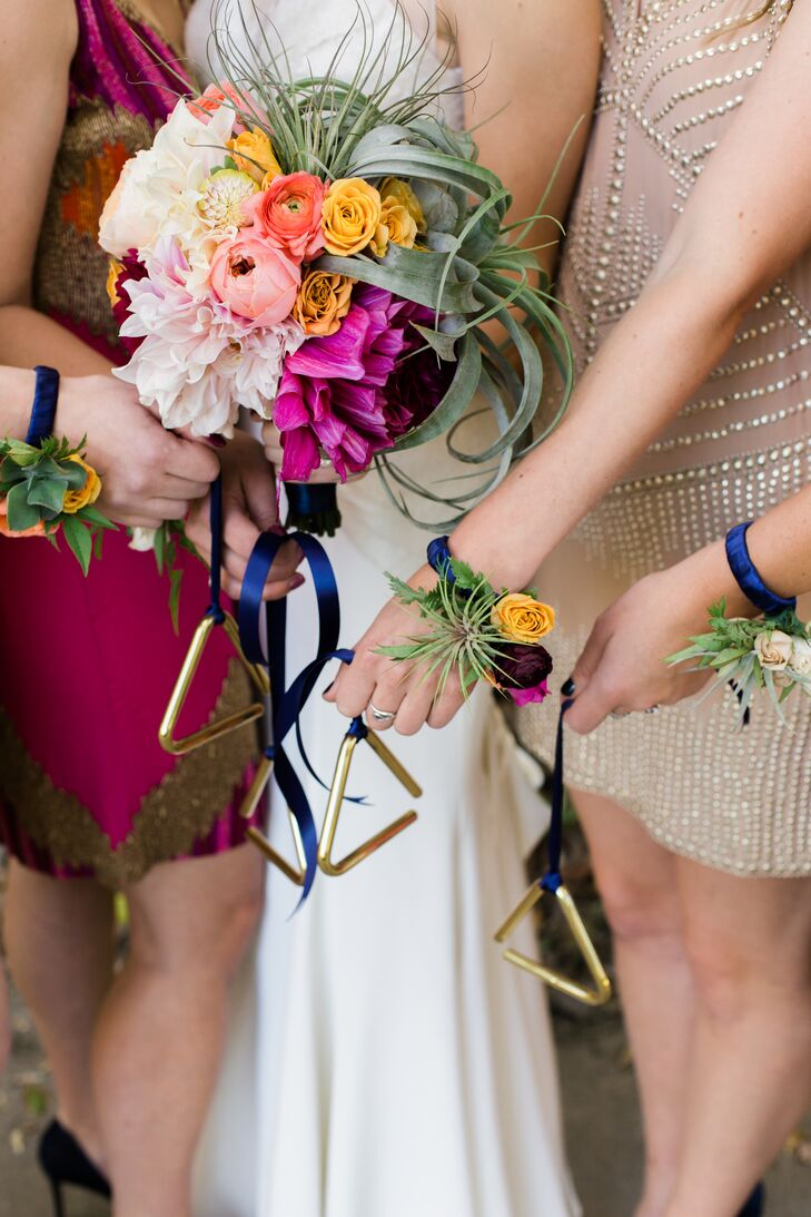Instead of traditional bouquets, the girls carried a triangle instrument corsage adorned with vibrant ranunculus blooms and tiny air plants. A blue ribbon was designed to hang from the bridesmaid's wrist so they could provide a soft beat as they walked down the aisle.