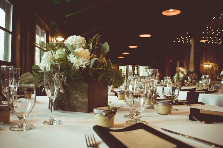 White and green flowers were set in wooden boxes for low centerpiece decor during the reception.