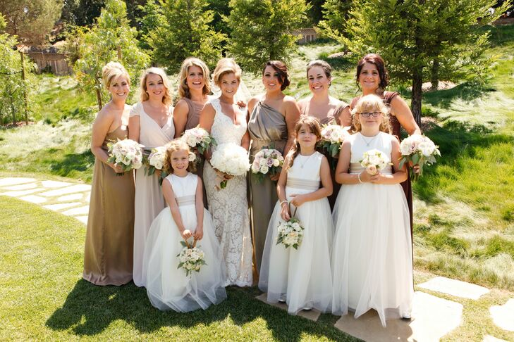 Keeping with the bride's earth tone color palette, bridesmaids wore floor-length dresses in different natural hues of brown and tan while flower girls wore white sleeveless dresses with neutral sashes.