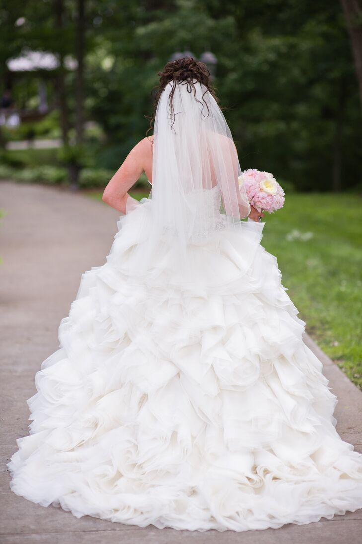 Kylie wore an ivory organza ruffled Lazaro ball gown with a sweetheart neckline and lace bodice.