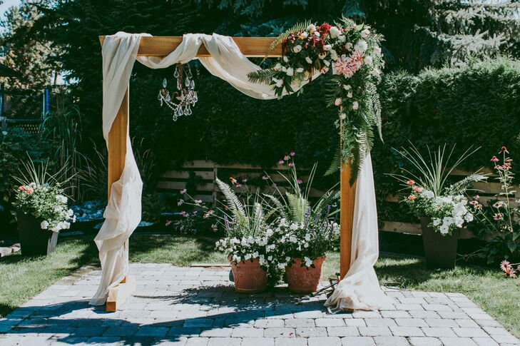 """Another good friend took on the enormous task of decorating the arbor with another floral arrangement and tulle, which we had previously purchased from a local Fabricland,"" Rebecca says."