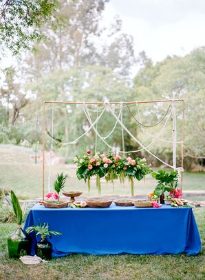 Buffet-Style Food Spread Topped with Hanging Tropical Leaves and Flowers