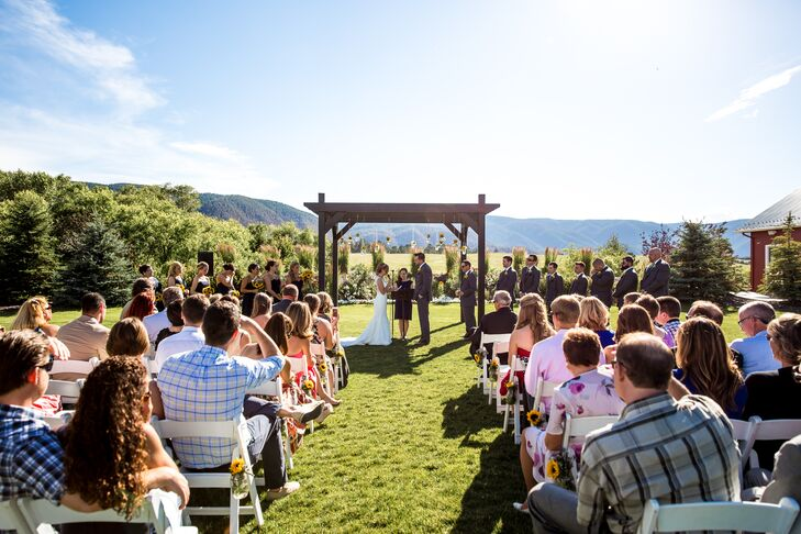 Kerry and Billy's reception took place outside at Crooked Willow Farms in Larkspur, Colorado. Since the space was naturally beautiful on its own—with those rolling foothills and lush lawns—they kept their decor simple. They hung sunflowers in mason jars from the wedding arbor and lined the aisle with sunflower blooms as well.