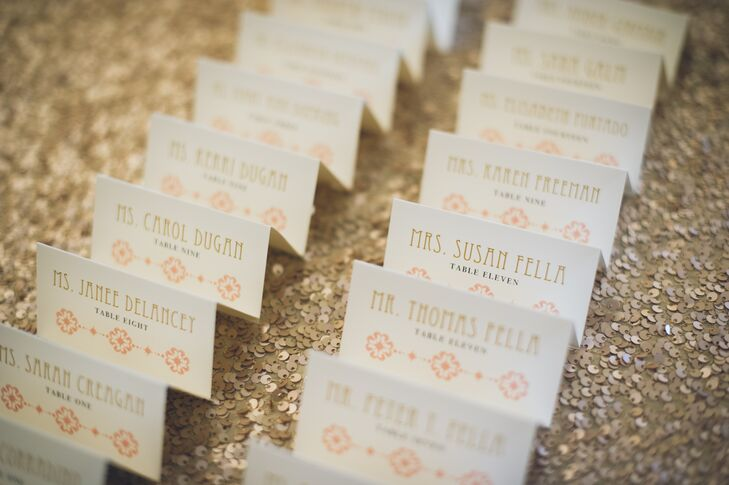 "Their escort display incorporated almost every part of the couple's color scheme as well as their want for ""glitzy accents. Placed above a gold sequin linen from La Tavola, each ivory escort card stood out with gold, art deco-worthy font and a geometric peach design. Black table numbers separated the two."