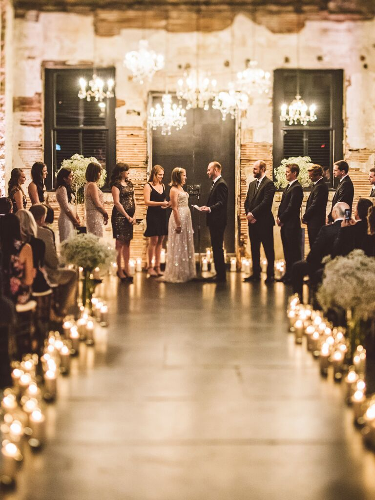 Industrial wedding ceremony space with chandeliers and candles