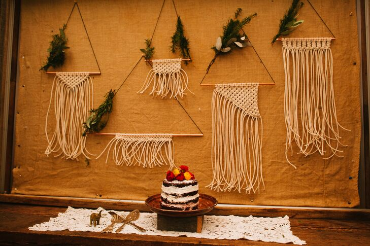 Handmade yarn macrame in different shapes and sizes hung from brass triangles, accented with greenery sprigs. The display served as the backdrop for the small naked wedding cake.