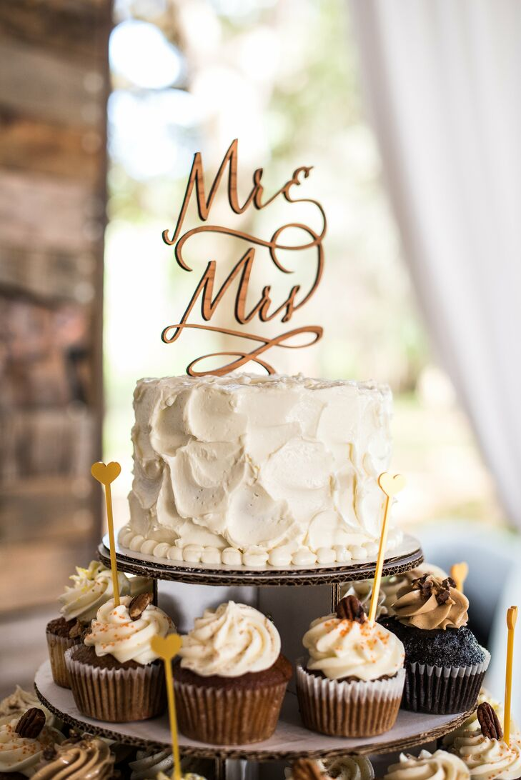 """They wanted a little variety for the dessert table, so Angela and Landon chose a single-tier Key lime cake from Sassy Cakes, served over several tiers of cupcakes. Each one was filled with pumpkin, carrot cake, whisky vanilla, lemon basil and peanut butter chocolate cupcakes. A canary yellow heart accent decorated every other treat and matched the cake's """"Mr."""" and """"Mrs."""" topper. As a family tradition, Angela's family also contributed nine flavors of cookies for some serious after-dinner treats."""