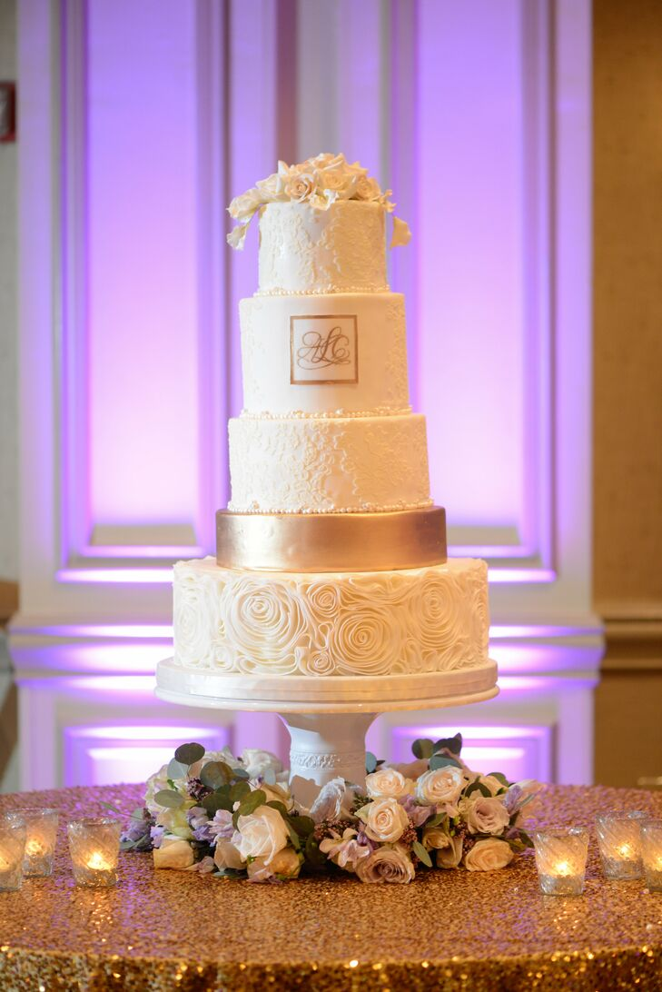 Minette from Custom Cakes created this five-tier confection based on Amanda's dress, incorporating the Chantilly lace from the bodice on the top layers and the rosettes from her ball gown skirt. A single gold tier and the newlyweds' custom monogram added a touch of glam.