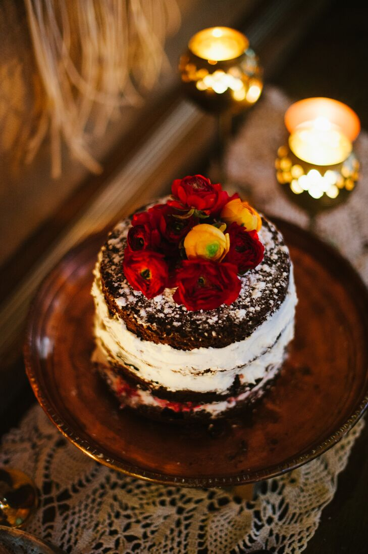 Paula and Nik cut into the small three-layer dark chocolate naked cake, filled with vanilla cream and powered with sugar. The dessert had red and yellow blooms decorating the top, all created by Paula.