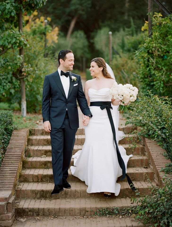 Bride in White Dress With Black Sash Holding Groom's Hand