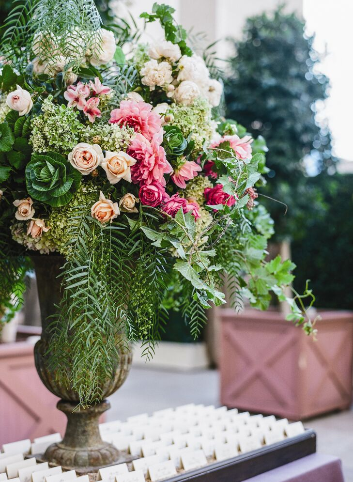 In the center of the escort card table was a large stone urn filled with a wild assortment of ferns, kale, roses and vines.