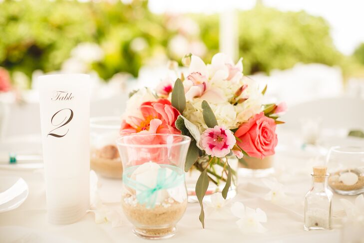 Tall circular black-and-white numbers marked each dining table at the tented reception, positioned next to glass containers filled with seashells and sand that fit the beach theme.