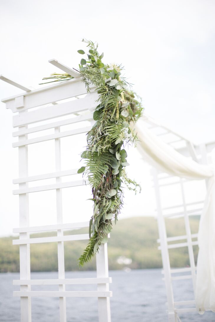For the ceremony, Katherine and Jon decided to keep the decor simple to avoid detracting from the beauty of the lakefront setting. They opted to forgo aisle arrangements, focusing the decorative touches on the simple white wedding arbor that stood along the shore, dressing it up with a panel of light, airy fabric and a small garland of cascading ferns, eucalyptus and vines.