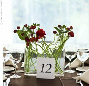Clear glass vases of varying sizes and shapes filled with spindly ranunculus sat atop dark chocolate tablecloths. Votives candles and small iron lanterns also adorned each table.