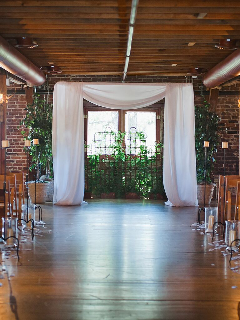 Rustic Indoor Ceremony With Wide Draped White Fabric And Greenery Backdrop