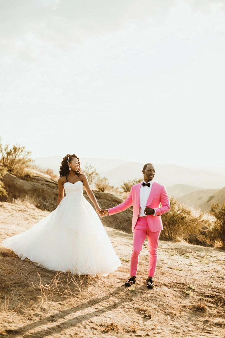 """A wedding is the one day couples don't usually take fashion risks, but I wanted my personality to shine through—and to do so with a little flair,"" John says. ""Because my mom passed away in 2008 from breast cancer, I decided to go with a pink suit."""