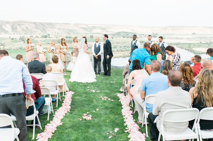 """We wanted it to be outdoors, even though August is very hot,"" Amber says. ""I wanted a venue so beautiful that I didn't have to have any decorations. I really didn't want an arbor or anything like that. I just wanted a beautiful scenic backdrop. When we found our venue [Fox Canyon Vineyards in Marsing, Idaho], I immediately knew it was the one. It was a winery overlooking a river canyon just outside Boise. The only decoration at the ceremony was a wine barrel, which held some items used in our ceremony, and blush and ivory rose petals sprinkled on both sides of the aisle."""